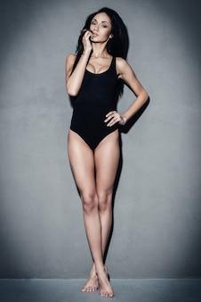 Кокетливая и шикарная. полная длина красивой молодой африканской женщины в черном купальнике, держащей руку на бедре и смотрящей в камеру, стоя на сером фоне