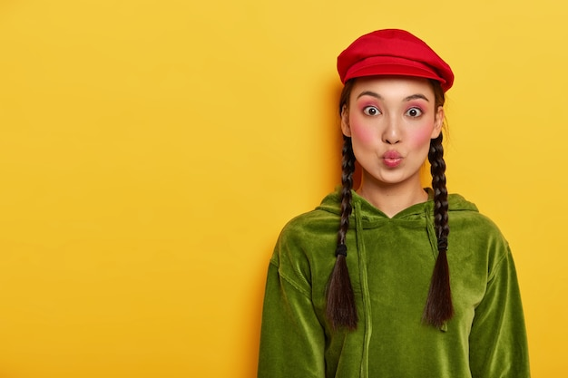 시시덕 거리는 아름다운 십대는 입술을 접고, 밝은 화장을하고, 세련된 빨간 모자와 코듀로이 스웻 셔츠, 두 개의 땋은 머리를 입고