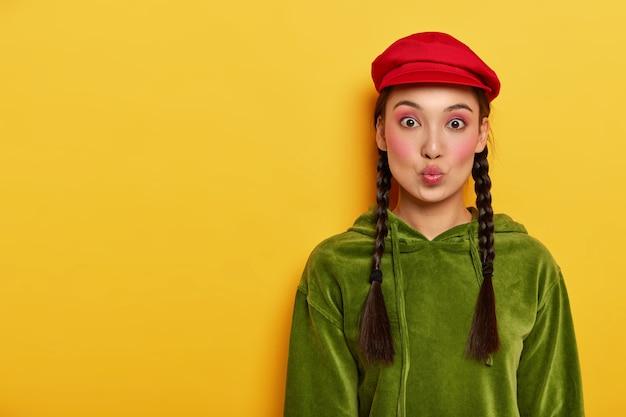 Flirty bella adolescente piega le labbra, indossa un trucco luminoso, vestito con un elegante cappello rosso e una felpa di velluto a coste, due trecce