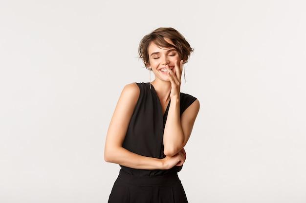 Кокетливая красивая женщина хихикает и прикрывает улыбку рукой, действуя кокетливо над белой.