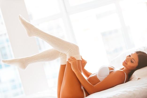 Кокетливая красотка. красивая молодая улыбающаяся женщина в нижнем белье, снимающая свои белые носки, лежа в постели и перед окном