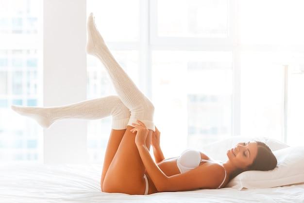 Кокетливая красотка в постели. красивая молодая улыбающаяся женщина в нижнем белье, снимающая свои белые носки, лежа в постели и перед окном