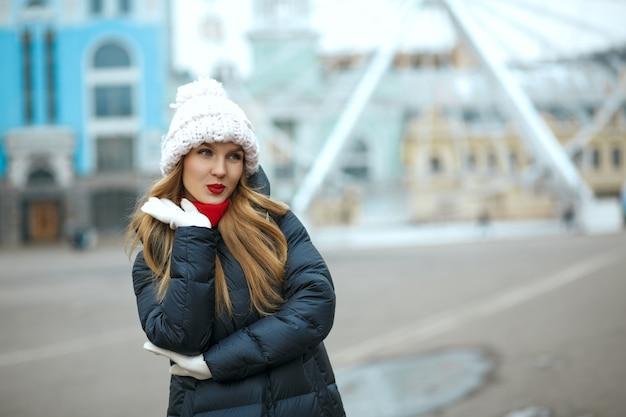 街歩きを楽しんで、ニット帽をかぶった赤い口紅で軽薄なブロンドの女性。テキスト用のスペース