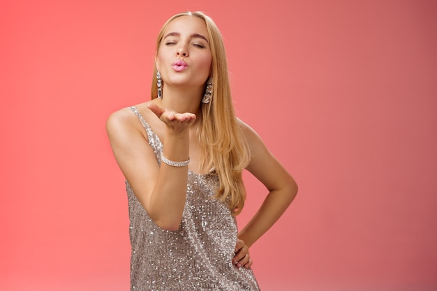 Flirty feminine carefree charming coquettish blond caucasian woman long hairstyle in silver dress hold hand fold lips send air kiss camera close eyes give passionate lovely mwah, red background.