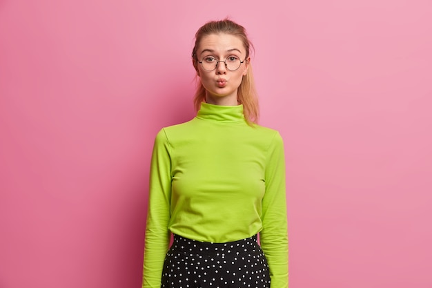 Flirty girl keeps folds lips in glamour way, sees handsome guy, flirts, wants to kiss someone, wears green turtleneck, round big spectacles