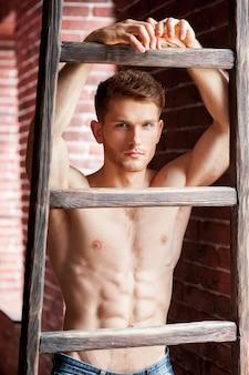 軽薄なハンサム。木製のはしごに寄りかかって、レンガの壁の近くに立っている間カメラを見ているハンサムな若い上半身裸の男
