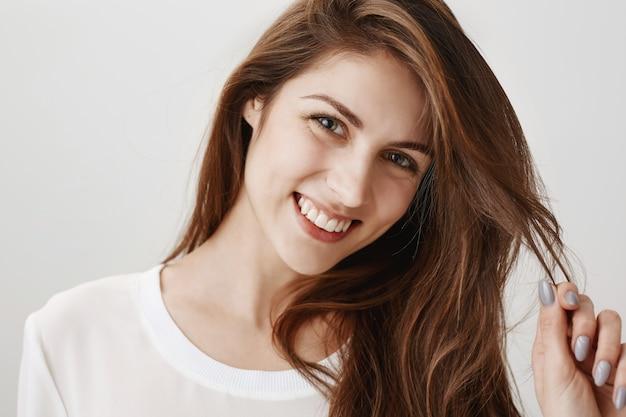 Кокетливая счастливая женщина играет с волосами и улыбается