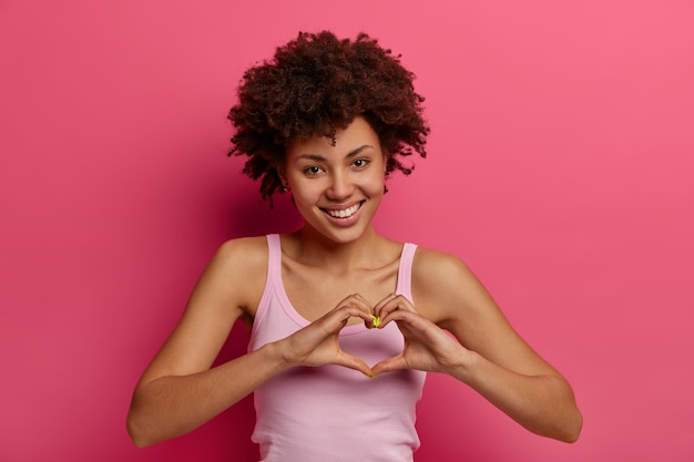 Flirty happy young curly woman expresses love and affection, makes heart gesture, shows what you mean to her, thanks dear friend for help, has charming tender look, poses against rosy wall