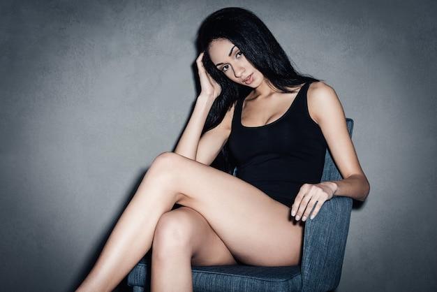椅子で軽薄。カメラを見て、灰色の背景に椅子に座っている間、膝で足を組んでいる黒い水着の美しい若いアフリカの女性