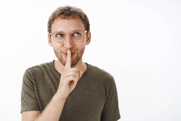 Flirty and naughty guy having intriguing secret, saying shh with index finger over mouth