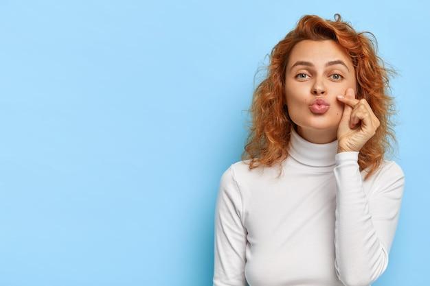 Flirty redhead caucasian woman keeps lips folded, gives tender romantic mwah