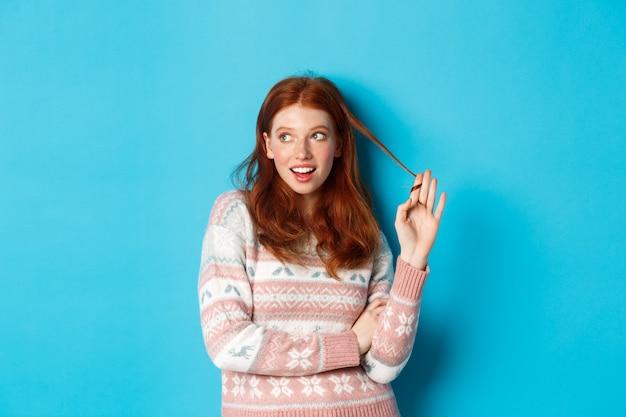 빨간 머리 소녀가 왼쪽을 쳐다보고, 머리카락을 가지고 놀고 생각하고, 파란색 배경 위에 서 있습니다.