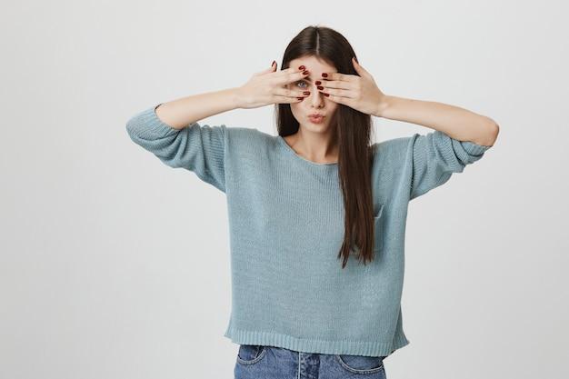 軽薄な笑顔の女性が目を覆い、指で覗く