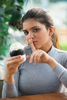 Flirty woman with finger on lips holding pastry