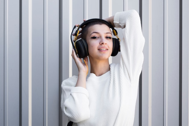 Flirty young female with shaved head wearing headphones