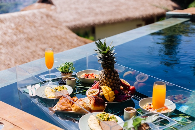 Floating breakfast at amazing hotel villa in blue swimming pool