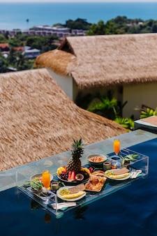 青いプールの素晴らしいホテルの別荘でのフローティング朝食