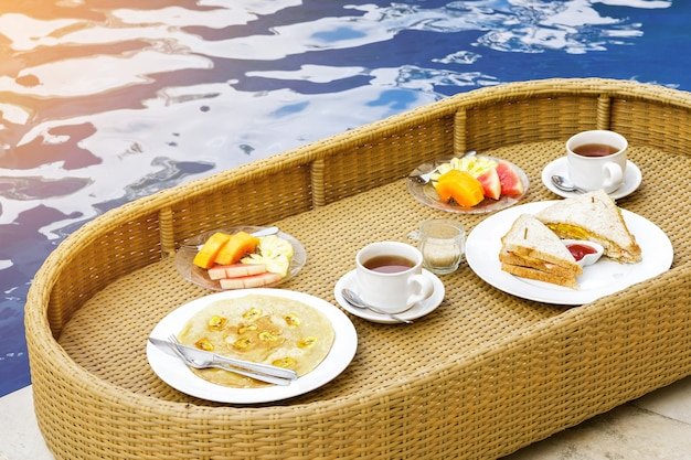 Floating breakfast in the swimming pool. straw tray with different food.