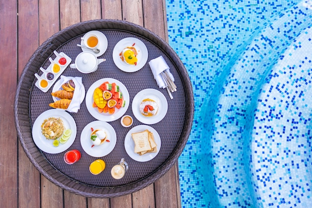 Floating breakfast tray around outdoor swimming pool with bread fruit egg coffee and juice