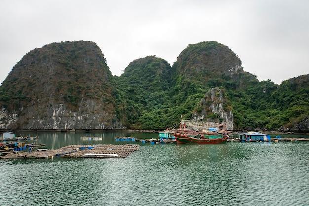 ベトナム、南シナ海のトンキン湾にあるハロン湾、降順ドラゴン湾に浮かぶ漁村。カルストタワーによって形成された風景-さまざまなサイズと形の島。