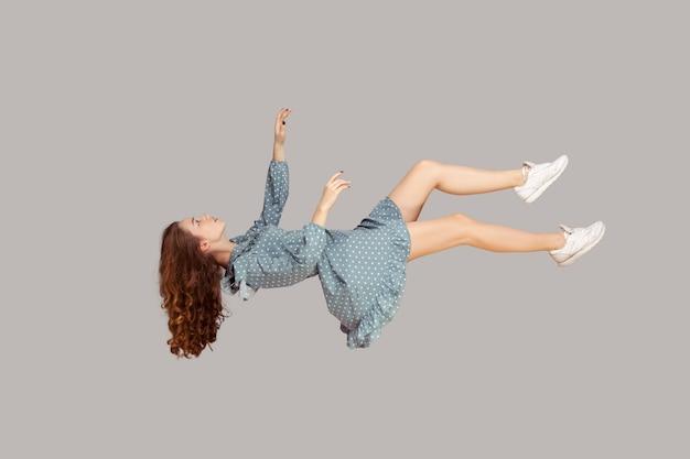 Парящий в воздухе. расслабленная девушка левитирует с закрытыми глазами, спит во время полета в воздухе