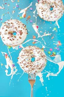 青色の背景に空気ドーナツに浮かんでいます。お菓子、ペストリー。