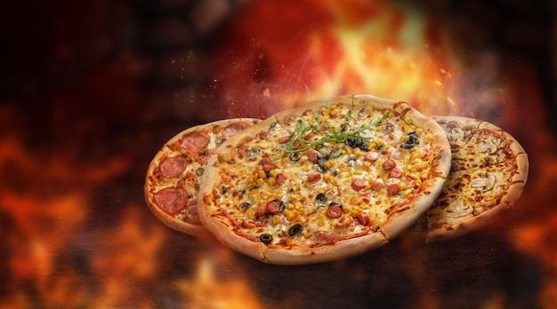Плавающая пицца в огне перед горящей печью. разные начинки. искры и дым.