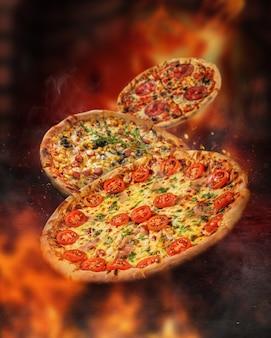 燃えるオーブンの前で炎に囲まれたフローティングピザ。さまざまなトッピング。火花と煙。