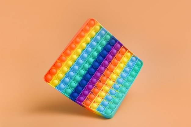 Floating rainbow silicone hands toy antistress pop it on color background. trendy children toy