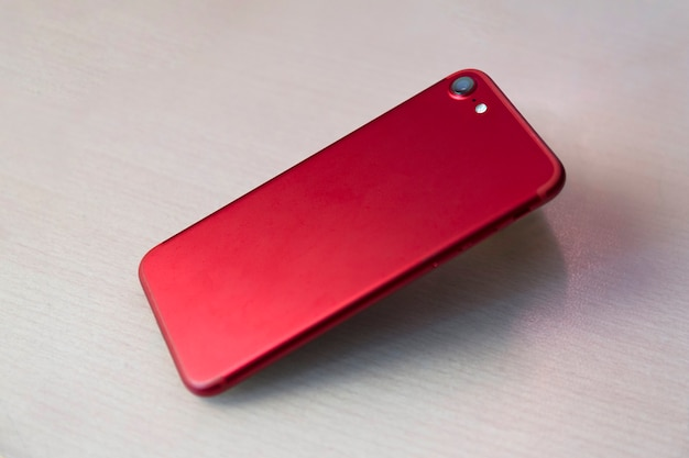 Floating red smartphone over wood