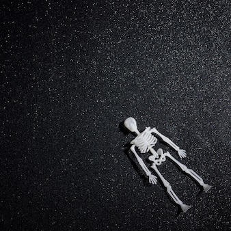 Floating skeleton over black glitter background
