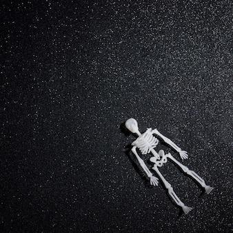 Scheletro galleggiante su sfondo glitter nero