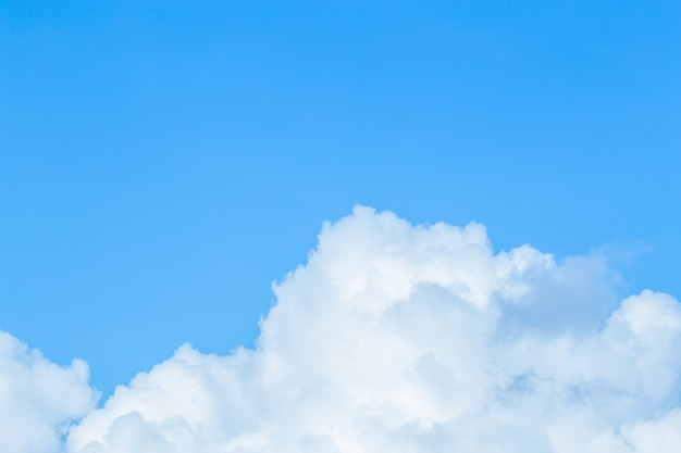 Floating white clouds and bright blue sky background