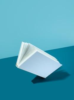 대담한 색상의 파란색-청록색-청록색 배경에 떠 있는 흰색 표지 책. 단단한 그림자가 있는 현대적인 사진입니다. 아이소메트릭 대각선 투영. 개념 국가 책 연인의 날. 공간을 복사합니다.