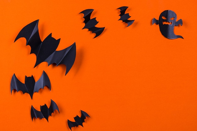 Flock of black paper bats and ghost on orange paper background.