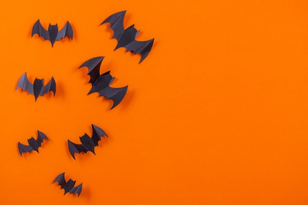 Flock of black paper bats on orange paper background.