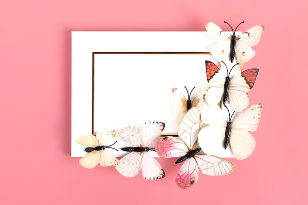 Flock of butterflies on white photo frame on pink background