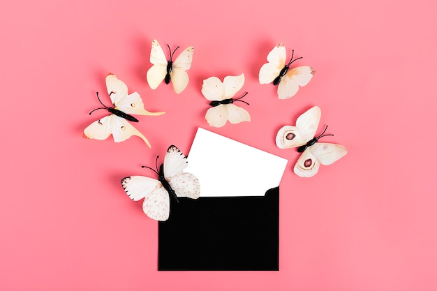 Flock of cabbage butterflies fly out from black envelope on pink background
