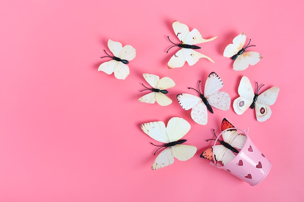 Flock of cabbage butterflies fly out from bucket with heart on pink background