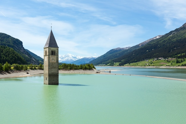 Flooded (in 1950) bell tower in reschensee and family (italy, church building in 14th-century)