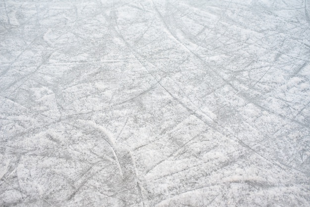 Floor background of a frozen ice rink with skate marks, with white snow during the winter.