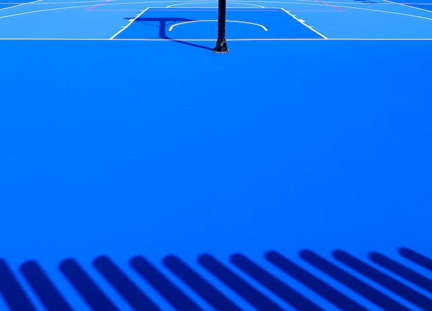 Floor background of an intense blue sports field with white lines.