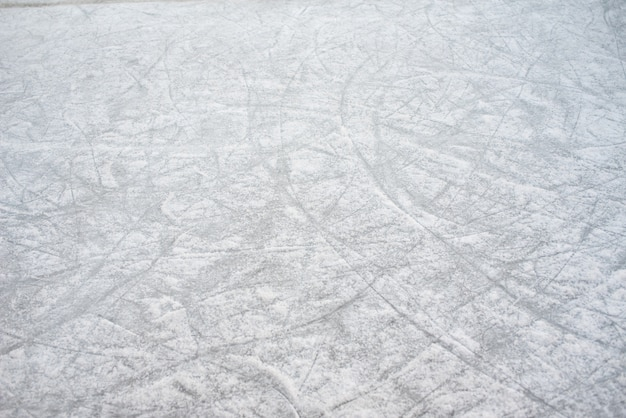 Предпосылка пола замороженного катка с метками конька, с белым снегом в течение зимы.