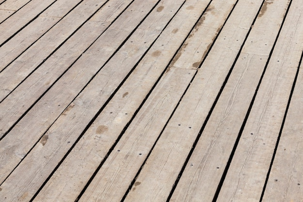 Floor boards in the gazebo. darkened wooden surface from the environment. photo close up