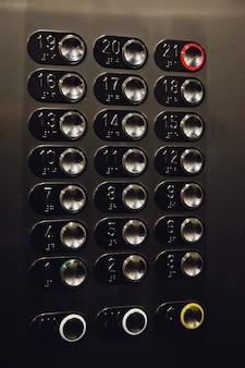 층 버튼 아파트 주거용 건물에 엘리베이터입니다. 리프트 패널 클로즈업의 버튼입니다. 운동, 교통 개념입니다. 벽에 많은 버튼. 엘리베이터 제어판의 숫자가 켜져 있습니다.