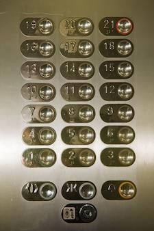 21번 21번이 눌려진 엘리베이터의 바닥 버튼. 다층 건물에서 클로즈업된 엘리베이터 움직임을 위한 크롬 제어판. 교통, 교통. 엘리베이터 벽에 많은 버튼