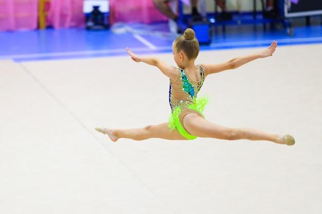 체조 선수권 대회 고품질 사진에서 바닥 운동 분할 점프 여자 체조 선수