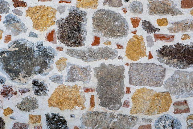 Floor gravel pebble stone on concrete wall background or fence texture made of a close up of medieval stone walls with colorful pebbles. abstract pebbles mosaic tiles design
