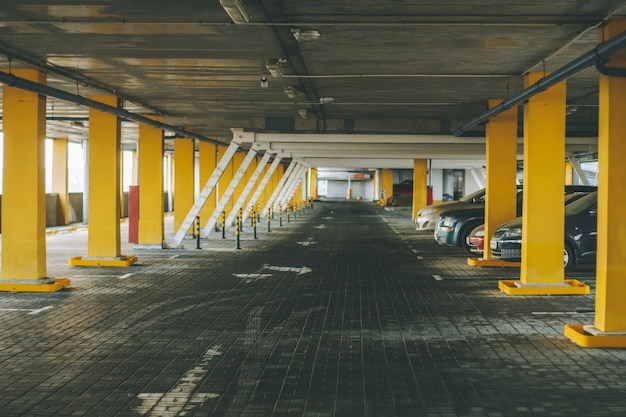 Floor of above-ground multi-level car park, with rows of yellow columns