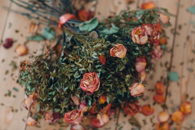바닥에 마른 오래된 장미 꽃다발이 놓여 있습니다.